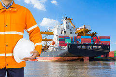 Engineer dockers wearing safety coat and holding a helmet. In front of an industrial harbor with cranes and a container ship being unloaded for logistic Import Royalty Free Stock Photography