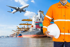 Engineer dockers wearing safety coat and holding a helmet. In front of an industrial harbor with cranes and a container ship being unloaded for logistic Import Royalty Free Stock Photos