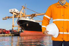 Engineer dockers wearing safety coat and holding a helmet. In front of an industrial harbor with cranes and a container ship being unloaded for logistic Import Stock Images