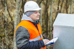 Engineer with documentation near electric enclosure. In winter day Stock Photography