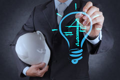 Engineer drawing lightbulb and construction Royalty Free Stock Image