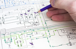 Engineer drawing on plan of gas plant. Royalty Free Stock Photo