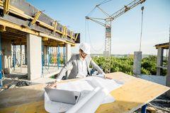 Engineer with drawings on the structure. Handsome engineer working with architectural drawings at the table on the construction site outdoors royalty free stock images