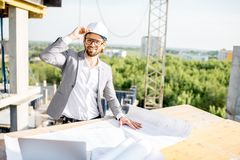 Engineer with drawings on the structure. Handsome engineer working with architectural drawings at the table on the construction site outdoors stock images