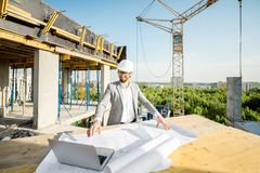 Engineer with drawings on the structure. Handsome engineer working with architectural drawings at the table on the construction site outdoors stock photos