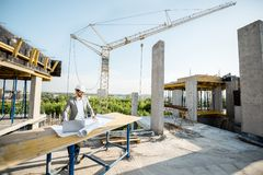 Engineer with drawings on the structure. Handsome engineer working with architectural drawings at the table on the construction site outdoors royalty free stock photos