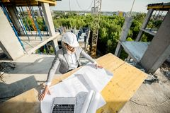 Engineer with drawings on the structure. Handsome engineer working with architectural drawings at the table on the construction site outdoors stock photo
