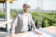 Engineer with drawings on the structure. Portrait of a funny engineer working with architectural drawings at the table on the construction site outdoors royalty free stock images