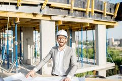 Engineer with drawings on the structure. Portrait of a funny engineer working with architectural drawings at the table on the construction site outdoors stock images