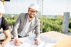 Engineer with drawings on the structure. Portrait of a handsome engineer working with architectural drawings at the table on the construction site outdoors stock photos