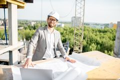 Engineer with drawings on the structure. Portrait of a handsome engineer working with architectural drawings at the table on the construction site outdoors stock photography