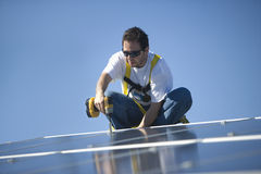 Engineer Drilling Solar Panel Against Blue Sky. Young engineer drilling solar panel while crouching against clear blue sky Stock Images