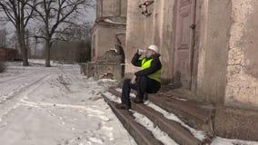 Engineer drink coffee near old building stock footage