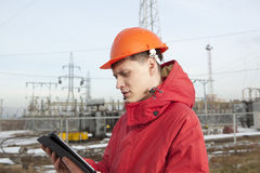 Engineer at electrical substation using a tablet computer Royalty Free Stock Photos