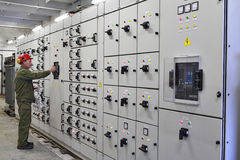 Engineer electrician switches switchgear equipment. Royalty Free Stock Photo