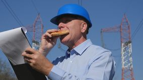 Engineer Electrician Working in Breakfast Time Eat and Read in Agenda royalty free stock images