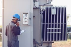 Engineer or electrician working on checking and maintenance equi. Pment at green energy solar power plant; checking status step up transformer high voltage at stock photo