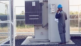 Engineer or electrician working on checking and maintenance equi. Pment at green energy solar power plant; checking status step up transformer high voltage at royalty free stock photography