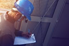 Engineer or electrician working on checking and maintenance equi. Pment at green energy solar power plant; checking status step up transformer high voltage at stock images