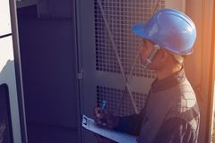 Engineer or electrician working on checking and maintenance equi. Pment at green energy solar power plant; checking status step up transformer high voltage at stock photography
