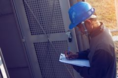 Engineer or electrician working on checking and maintenance equi. Pment at green energy solar power plant; checking status step up transformer high voltage at stock image