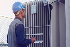 Engineer or electrician working on checking and maintenance equi. Pment at green energy solar power plant; checking status step up transformer high voltage at royalty free stock image