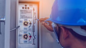 Engineer or electrician working on checking and maintenance equi. Pment at green energy solar power plant; checking status step up transformer high voltage at royalty free stock images