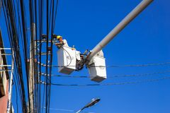 Engineer electricians repairing electricity power line at high place of electric pole. On crane against blue sky stock images