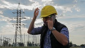 Engineer electricity talking phone during sunset stock video footage