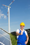 Engineer at energy park with solar panels and wind turbine Stock Image