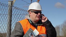 Engineer with euro banknotes talking on cell phone stock video