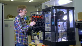 An engineer examines a big mesh 3d-printed piece. stock footage