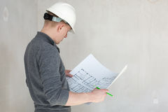 An engineer examining blueprints on a construction. A back view of an engineer in white helmet examining blueprints on a construction site royalty free stock photography