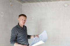 An engineer examining blueprints on construction. An engineer examining blueprints on a construction site royalty free stock photo