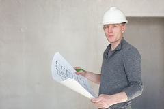 An engineer examining blueprints on construction site. An engineer examining blueprints on a construction site royalty free stock photo
