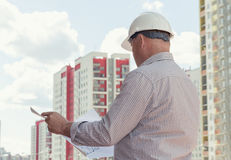 An engineer examining blueprints. An engineer holding blueprints on a background with buildings Royalty Free Stock Photography