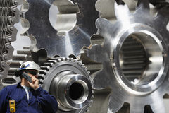 Engineer examining large gears and cog machinery Royalty Free Stock Image