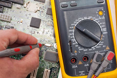 Engineer examining motherboard by multimeter Stock Image