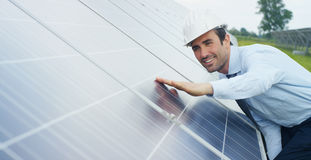 Engineer expert in solar energy photovoltaic panels with remote control performs routine actions for system monitoring using clean. Renewable energy. concept Royalty Free Stock Image