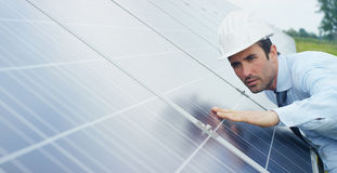 Engineer expert in solar energy photovoltaic panels with remote control performs routine actions for system monitoring using clean. Renewable energy. concept Royalty Free Stock Photos