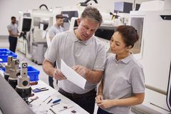 Engineer And Female Apprentice Discussing Job Sheet In Factory royalty free stock photo