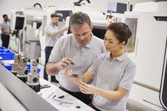 Engineer And Female Apprentice Measuring Components In Factory stock photos