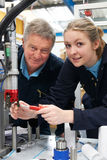 Engineer And Female Apprentice Working On Machine In Factory stock photos