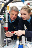 Engineer And Female Apprentice Working On Machinery In Factory royalty free stock image
