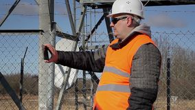 Engineer filmed at outdoors near metal structures stock video footage