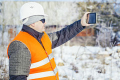 Engineer filmed with tablet PC destroyed building in winter Royalty Free Stock Images
