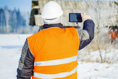 Engineer filmed with tablet PC destroyed building Royalty Free Stock Image