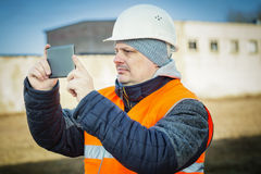 Engineer filmed with tablet PC near building Stock Photography