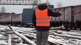 Engineer filmed on the tablet PC near the freight wagons stock video