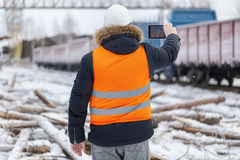Engineer filmed on the tablet PC near the freight wagons Royalty Free Stock Images